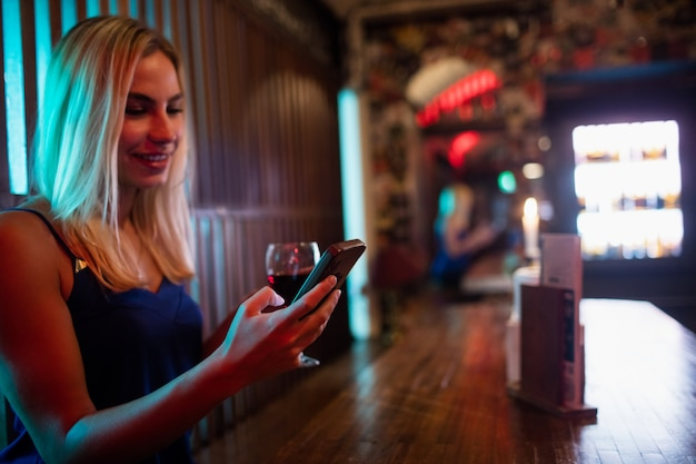 Mulher bonita usando o celular enquanto toma vinho tinto no balcão