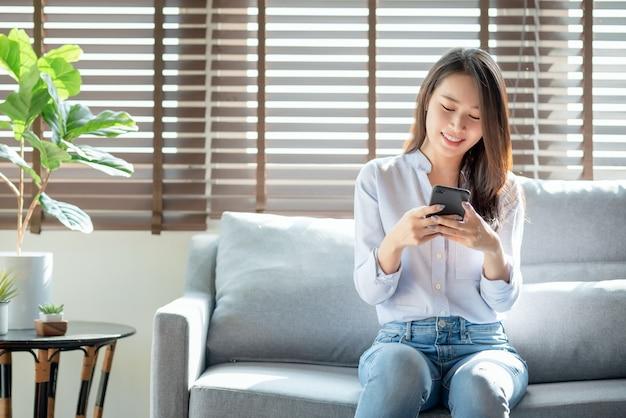 Mulher bonita usando o celular para bater um papo com as amigas em casa