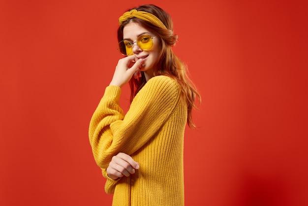 Mulher bonita usando óculos e suéter amarelo emoções casual wear fundo vermelho.