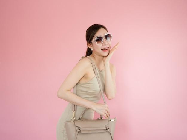 Mulher bonita usando óculos escuros e carregando sacolas de couro, conceito de moda