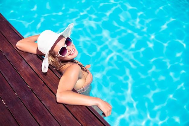 Mulher bonita usando óculos escuros e chapéu de palha encostado no deck de madeira ao lado da piscina