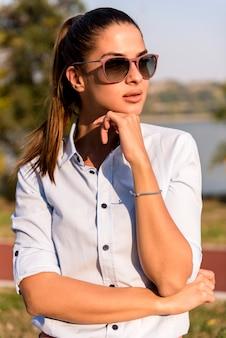 Mulher bonita usando óculos escuros posando no exterior