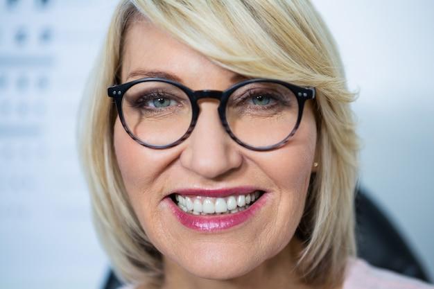 Mulher bonita usando óculos na loja de óptica