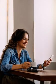 Mulher bonita usando seu celular na cafeteria.