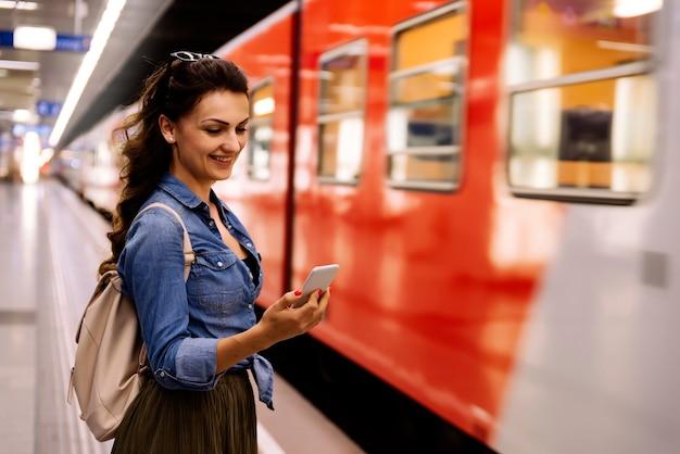 Mulher bonita usando seu telefone celular na plataforma do metrô. conceito de transporte.