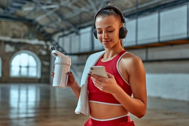 Mulher bonita usando smartphone e ouvindo música em fones de ouvido bebe shake de proteína durante o exercício na sala de fitness. conceito de esportes e tecnologia. tema de estilo de vida e saúde.