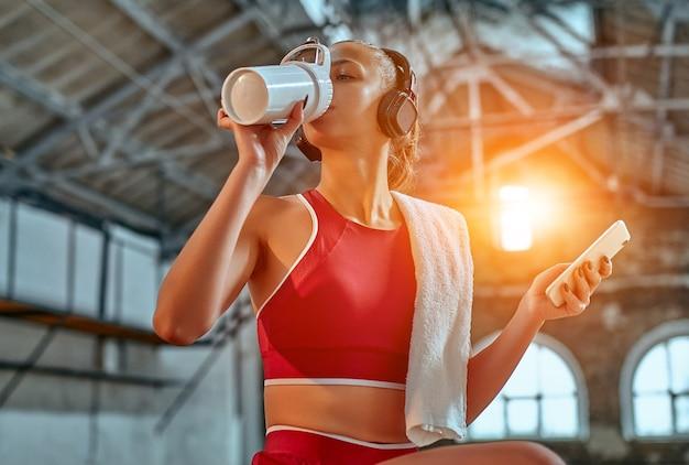 Mulher bonita usando smartphone e ouvindo música em fones de ouvido bebe shake de proteína durante o exercício na sala de fitness. conceito de esportes e tecnologia.