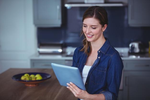 Mulher bonita usando tablet digital na cozinha