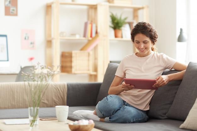 Mulher bonita usando tablet em casa
