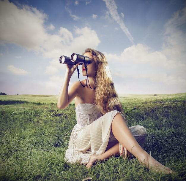 Mulher bonita usando um binóculo