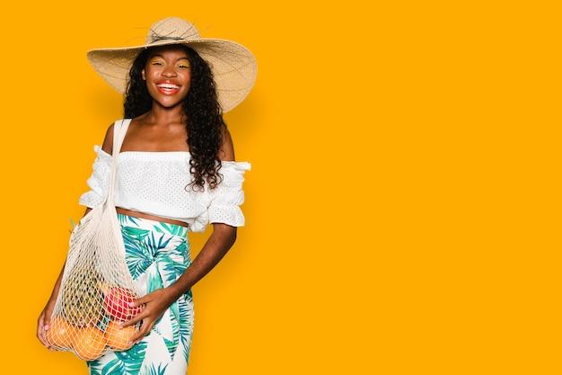 Mulher bonita usando uma bolsa de rede na compra de frutas