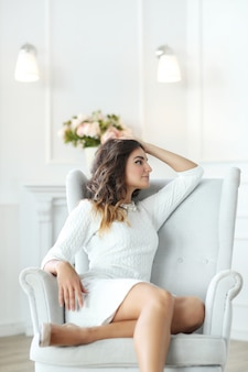Mulher bonita usando vestido branco e sentado na poltrona branca