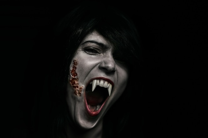 mulher bonita vampira de halloween sobre preto