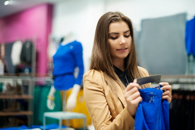 Mulher bonita verificando etiqueta em uma boutique