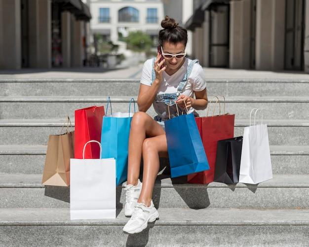 Mulher bonita verificando sacolas de compras