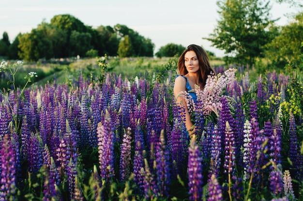 Mulher bonita, vestida com um vestido de tremoço de flores ao pôr do sol