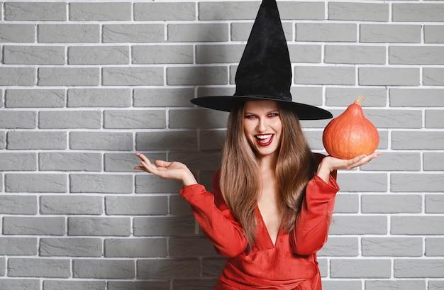 Mulher bonita vestida de bruxa para o halloween contra uma parede de tijolos
