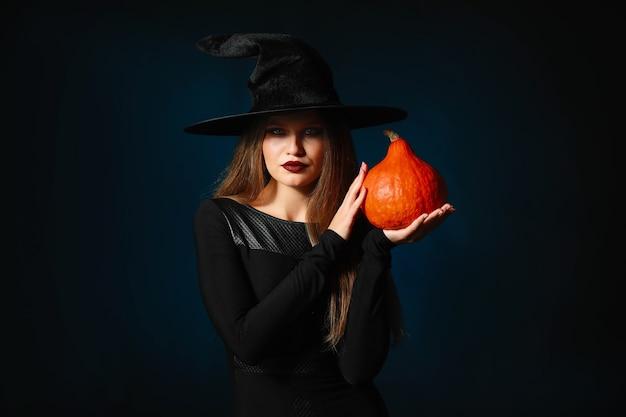 Mulher bonita vestida de bruxa para o halloween no escuro
