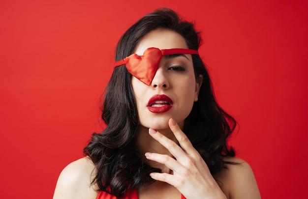 Mulher bonita vestida de vermelho com tapa-olho em forma de coração