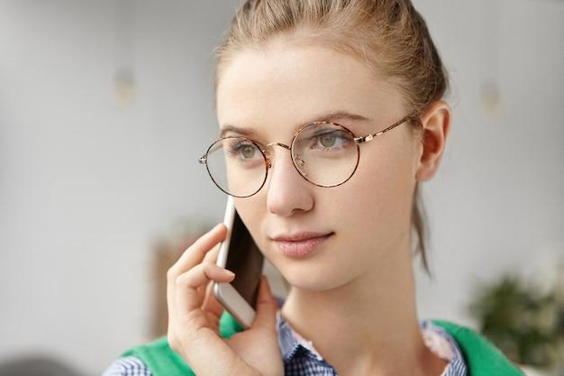 Mulher bonita vestida formalmente no escritório com telefone