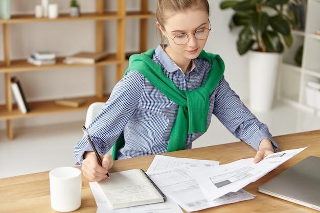 Mulher bonita vestida formalmente no escritório escrevendo