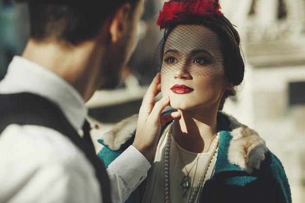 Mulher bonita vestida no estilo dos anos 30 fica na rua e olha para o homem com amor