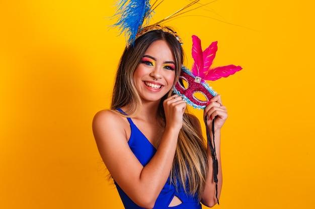 Mulher bonita vestida para a noite de carnaval. mulher sorridente pronta para curtir o carnaval com máscara