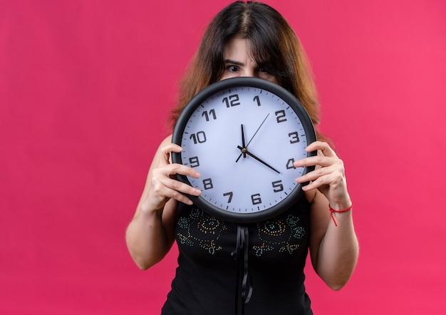 Mulher bonita vestindo blusa preta se escondendo atrás do relógio sobre fundo rosa