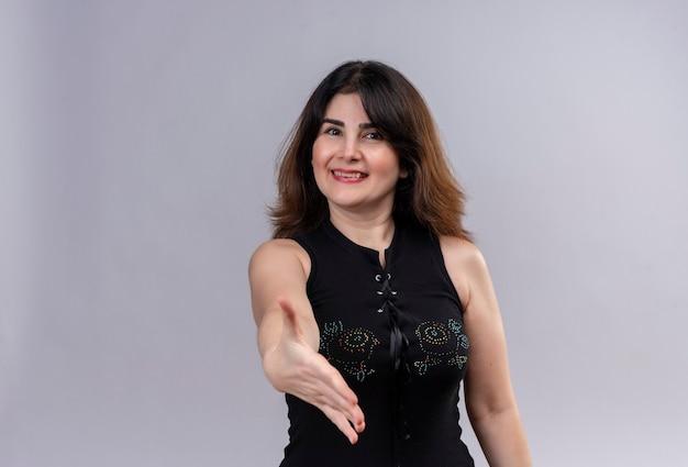 Mulher bonita vestindo blusa preta sorrindo calorosamente e dando boas-vindas