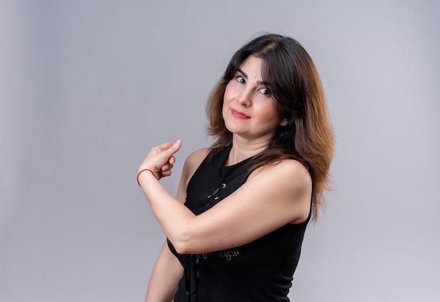 Mulher bonita vestindo blusa preta sorrindo, mostrando as costas com o indicador