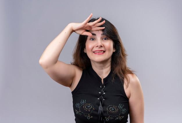 Mulher bonita vestindo blusa preta sorrindo procurando por alguém