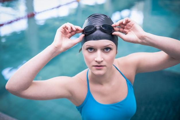 Mulher bonita vestindo boné de natação e óculos de natação na piscina