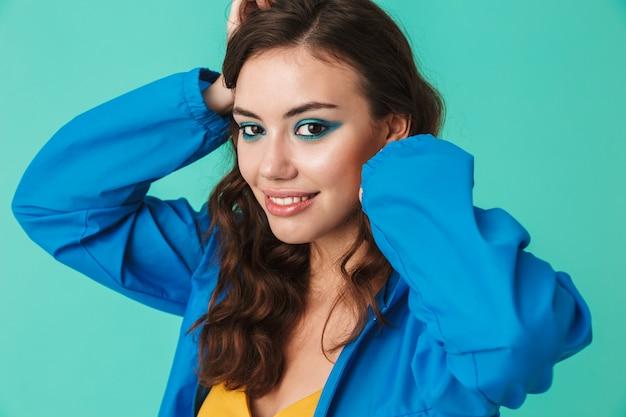 Mulher bonita vestindo capa de chuva ou jaqueta sorrindo e segurando as mãos na cabeça