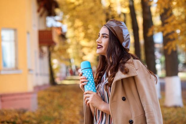 Mulher bonita vestindo casaco bege e boina de couro. senhora romântica está segurando caneca térmica azul polka dot nas mãos