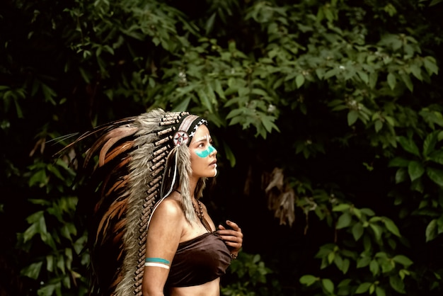 Mulher bonita vestindo cocar penas de pássaros.