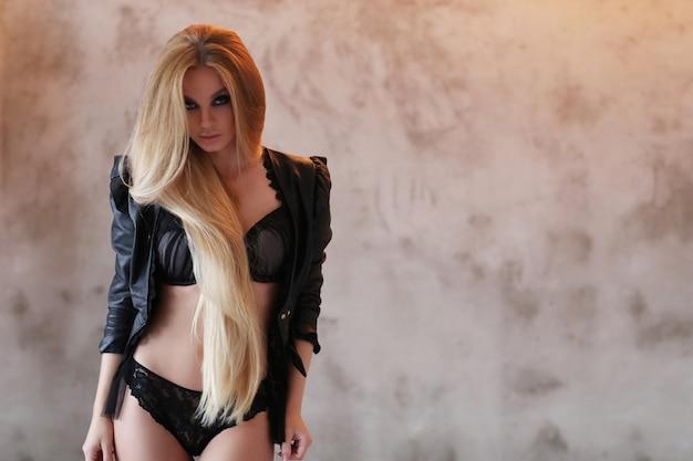 Mulher bonita vestindo jaqueta de couro preta e lingerie preta sexy