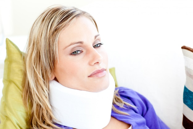 Mulher bonita vestindo neckbrace deitado em um sofá