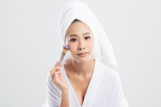 Mulher bonita vestindo roupão de banho com toalha com toalha na cabeça está usando um pincel de maquiagem maquiagem após banho de fundo branco.