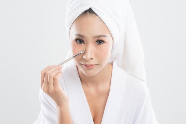 Mulher bonita vestindo roupão de banho com toalha com toalha na cabeça está usando uma maquiagem pincel de maquiagem em fundo branco.