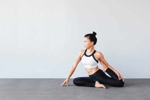 Mulher bonita vestindo sportswear praticando yoga no estúdio