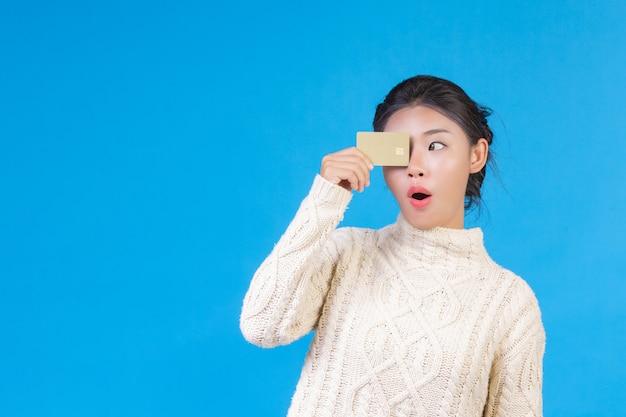 Mulher bonita, vestindo um novo tapete branco de mangas compridas, segurando um cartão de crédito dourado em um azul. negociação.