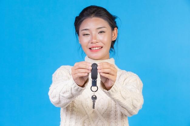 Mulher bonita, vestindo um novo tapete branco de mangas compridas, segurando um chaveiro na mão em um azul. negociação s.