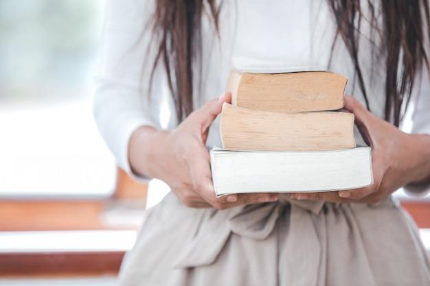 Mulher bonita, vestindo uma camiseta branca, segurando livros