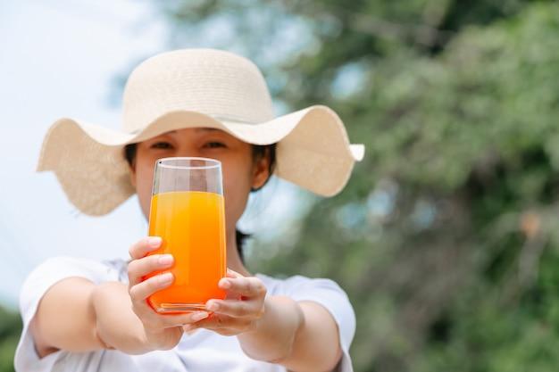 Mulher bonita, vestindo uma camiseta branca, segurando um copo de suco de laranja