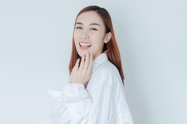 Mulher bonita vestir camisa branca sorrir no quarto de cama na manhã