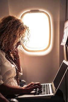 Mulher bonita viaja em um vôo de avião e usa um laptop pessoal a bordo com conexão à internet para trabalhar
