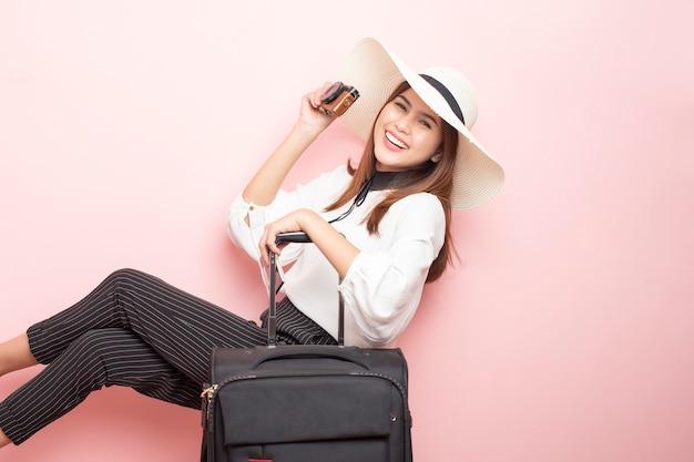 Mulher bonita viajante é emocionante em fundo rosa