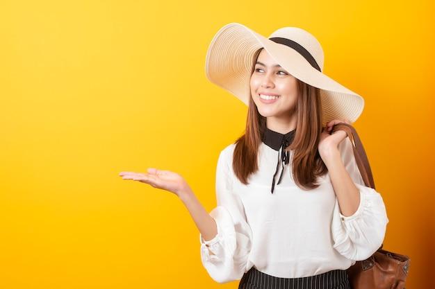 Mulher bonita viajante é emocionante na parede amarela