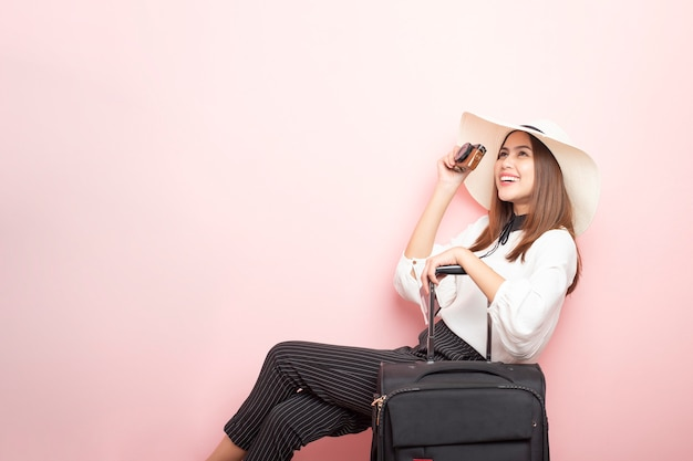 Mulher bonita viajante é emocionante na parede rosa
