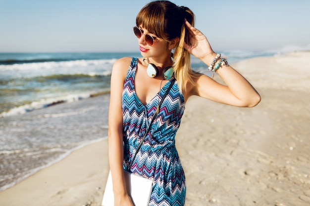 Mulher bonita viajante usando tablet na praia ensolarada